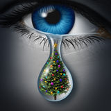 Holiday Depression. And winter season anxiety and emotional crisis concept as a human eyeball crying a tear with a christmas tree inside as a metaphor for Royalty Free Stock Image