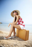 Holiday destination. Young femaled styled in 50s summer outfit sitting on a retro suitcase on the beach Stock Photos