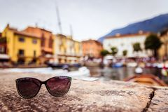Holiday destination: Sunglasses on the ground, blurry Italian village in the background. Italian harbour scene: Sunglasses on the stony ground holiday summer stock photo