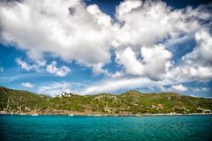 Holiday destination while travelling and wanderlust. Mountain shore in blue sea on cloudy sky in gustavia, st.barts. Summer vacati. On on tropical island. Wild Stock Photos