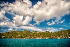 Holiday destination while travelling and wanderlust. Mountain shore in blue sea on cloudy sky in gustavia, st.barts. Summer vacation on tropical island. Wild stock photography