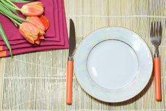 Holiday dinner. White plate and orange covers with tulips Royalty Free Stock Photos