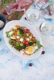 Holiday dinner. Salad with vegetables, shrimps, egg. Two glasses of wine. Light table. stock image