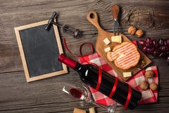 Holiday Dinner setting with red wine and creaming cheese on rustic wood royalty free stock photo