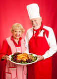 Holiday Dinner Teamwork. Senior couple works together to prepare a delicious holiday meal Stock Photos