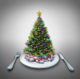 Holiday Dinner. And winter celebration food recipe as a decorated pine christmas tree on a table setting with a plate fork and knife as a symbol of eating Royalty Free Stock Photo