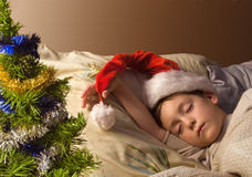 Holiday dream-1. Little boy in Santa's hat sleeping next to Christmas tree Royalty Free Stock Images