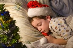 Holiday dream-2. Little boy in Santa's hat sleeping next to Cristmas tree Royalty Free Stock Photography