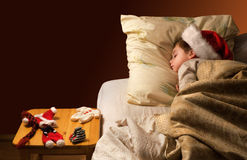 Holiday dream-4. Little boy sleeping next to Santa's uniform laying on a stool Royalty Free Stock Photo