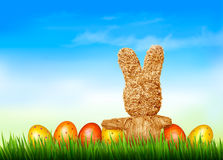 Holiday Easter background with straw rabbit and easter eggs. Stock Images