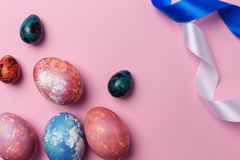 Holiday Easter eggs with white and blue ribbon on pink background royalty free stock photos