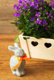 Holiday Easter rabbit and beautiful flowers campanula. Holiday Easter rabbit and beautiful flowers campanula on wooden background stock images