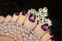 Holiday elegant purple pedicure. Holiday elegant purple pedicure with rhinestones on a black background with jewelry royalty free stock images