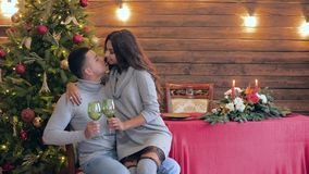 Holiday emotions, girl sits on arms of spouse and kisses him with green glasses in hands on background of festive table. Holiday emotions, girl sits on arms of stock footage