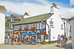 Holiday in the English Lake District. Queens Head at Hawkeshead in the English Lake District with people sitting out drinking in the sunshine and walkers Stock Photo