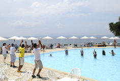 Holiday entertainer. Dancing at the swimming pool, tourists swim in the blue water, nissaki beach of the greek island of corfu, ionian sea (part of the stock images
