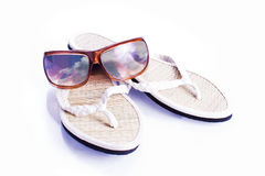 Holiday essentials. A pair of flip flops and sunglasses in a holiday themed still life stock images