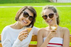 Happy young mother and cute daughter of a teenager in a city park eating ice cream, talking and laughing. Holiday with the family. Happy young mother and cute Royalty Free Stock Images