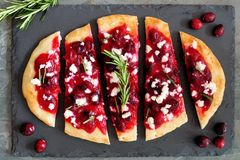 Holiday flatbread appetizer with cranberries and goat cheese on slate Royalty Free Stock Photography