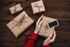 Holiday flatlay arrangement of wrapped presents on dark wooden background. Celebration concept royalty free stock photo
