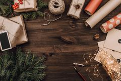 Holiday flatlay arrangement of wrapped presents on dark wooden background. With copyspace royalty free stock images