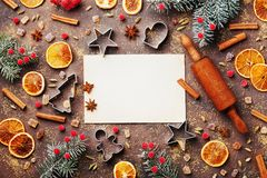 Holiday food background for baking gingerbread cookies with cutters, rolling pin and spices on table top view. Vintage paper sheet for christmas recipe Royalty Free Stock Photo