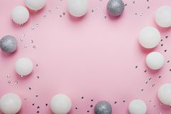 Holiday frame made of christmas balls and sequins on stylish pink table top view. Fashion background. Flat lay. Party mockup.