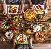 Holiday friends or family at the holiday table with rabbit meat, vegetables, pies, eggs, top view. Traditional Easter celebration, Easter holiday party. Holiday stock images