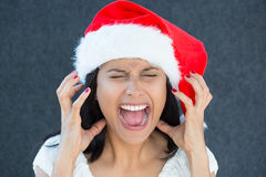 Holiday frustration. Closeup portrait of a cute Christmas woman with a red Santa Claus hat, white dress, screaming out loud, frustrated, eyes shut in rage Stock Image