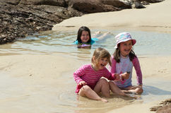 Holiday fun. Three kids having fun in the water at the beach Royalty Free Stock Images