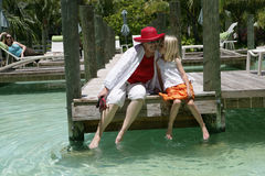 Holiday Fun. A woman and a little girl talking with each other while sitting on a wooden deck Royalty Free Stock Photos
