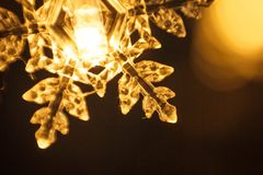 Holiday garland, clear plastic snowflake glows with a Golden light. royalty free stock photo