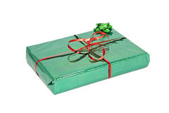 Holiday gift. Wrapped in shiny green paper, tied with a ribbon, closeup Stock Image