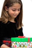 The Holiday Gift. Young girl looking at her present Stock Photography