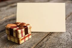 Holiday gift and card. Holiday gift and blank greeting card on wooden background royalty free stock image