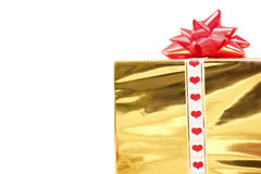 Holiday gift in box with gold foil and red bow Stock Images
