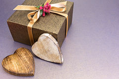 Holiday gift box with golden ribbon and wooden hearts stock photo