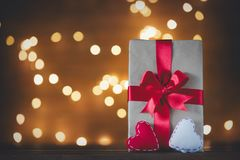 Holiday gift box and heart hape toy on Fairy Lights. Background Royalty Free Stock Images