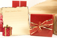 Holiday gift boxes decorated with ribbon and letter to Santa Claus isolated on white background. Stock Photo