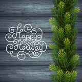 Holiday gift card with hand lettering Happy Holiday and Christmas borders from fir tree branches on wood background Royalty Free Stock Photo
