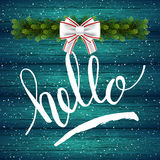 Holiday gift card with hand lettering Hello and Christmas celebration fir branch on wood background Stock Image