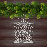 Holiday gift card with hand lettering Merry Christmas and Christmas borders from fir tree branches on wood background Stock Photo