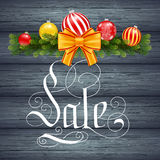 Holiday gift card with hand lettering Sale and Christmas celebration fir branch on wood background Stock Images