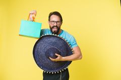 Holiday and gift concept. Man cheerful face sombrero hat holds shopping bag yellow background. Guy with beard festive in. Sombrero. Man festive mood holds stock photo