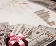 A holiday gift of money. Dollar billboards with a red satin ribbon and a box. Dollar billboards with a red satin ribbon and a box royalty free stock images