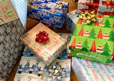Many gift boxes wrapped in Christmas themed gift wrap stock image