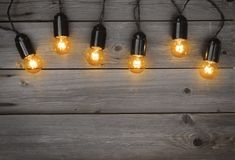 Holiday glowing garland of light bulbs on vintage wooden background Stock Images