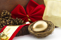 Holiday gold nest egg. Gold egg in twig nest with holiday red bow and pine cones in wood box offers a rustic view of financial savings and investment.  Gift of Royalty Free Stock Photo