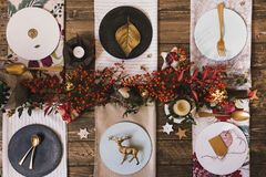 Holiday Gold place setting, funny Christmas table with ornaments. And natural berries, on wooden table, overhead shoot royalty free stock photo