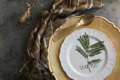 Holiday Gold place setting, napkin brown plaid, on grunge backgr Royalty Free Stock Photos